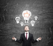 Man in search of solution. Young man standing in front of a black wall in posture of meditation with eyes closed, white light bulb above, looking for a solution Stock Images
