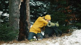 Man searches something in his backpack sitting in the winter forest covered with snow.  stock footage