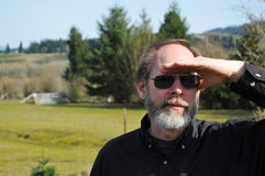 Man Searching. Senior man with his hand on his forehead to protect his eyes from the sun in order to search and salute Stock Images