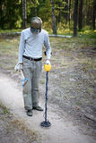 Man searching coins with metal detector Stock Photos