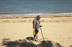 Man searching with metal detector on the beach with great expectations. A man searching the sand for coins or rings at the beach with a metal detector Stock Photo