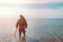 Man searching for a precious metal using a metal detector. Sea and sky on the background. Light from the left side royalty free stock photography