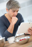 Man searching for recipe on tablet Royalty Free Stock Images