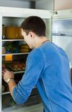 Man searching for something in refrigerator. At home Stock Images