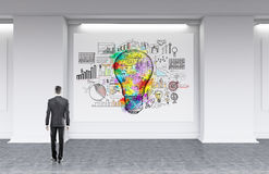Man searching for successful business route. Man in gray suit looking at whiteboard with sketch of colorful light bulb and small abstract images searching for Stock Image