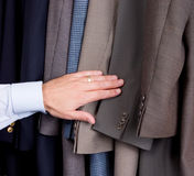 Man searching through suits. In the closet Stock Photo