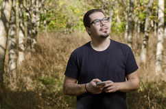Man searching telephone coverage in the forest Stock Images