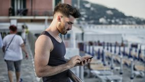 Man at the seaside using cell phone to type message. Athletic young man at the seaside using cell phone to type message while looking at the sea and beach Royalty Free Stock Image