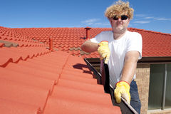 Man seasonal Gutter cleaning red roof stock photo