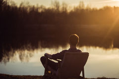 Man in the seat at bank of  lake also looks afar on sunset Stock Photos