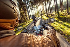 Man seat on the motorcycle on the forest road. Stock Image