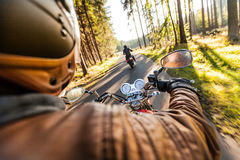 Man seat on the motorcycle on the forest road. Royalty Free Stock Image