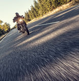 Man seat on the motorcycle on the forest road. Royalty Free Stock Photo