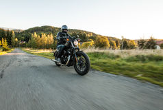 Man seat on the motorcycle on the forest road. Royalty Free Stock Photography