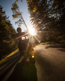 Man seat on the motorcycle on the forest road. Royalty Free Stock Images