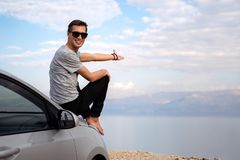 Man seated on the engine hood of a rented car on a road trip in israel stock photography