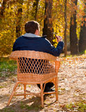 Man seated with his back in a cane chair Stock Photography
