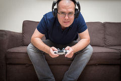 Man seated on a sofa with console controller in hands and playin Stock Images