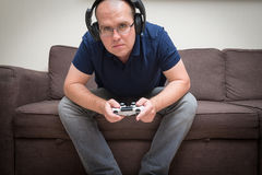 Man seated on a sofa with console controller in hands and playin Royalty Free Stock Photos