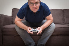 Man seated on a sofa with console controller in hands and playin Stock Photos