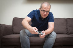 Man seated on a sofa with console controller in hands and playin Royalty Free Stock Images