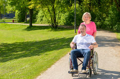 Man seated in wheel chair while wife pushes Royalty Free Stock Photos