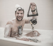 Man is seating in the foam bath with phone and camera in special bags Stock Photography