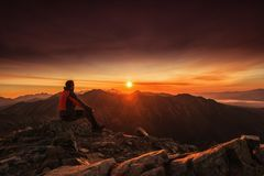 Man seating on the top of mountain at sunrise, hiking and climbing.  stock photography