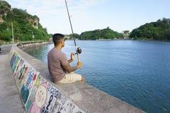 Man on seawall on vacation fishing. Man on seawall on vacation in Japan with T shirt fishing Royalty Free Stock Photos