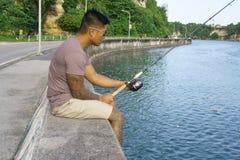 Man on seawall on vacation fishing 2. Man on seawall on vacation in Japan with T shirt fishing Stock Photography