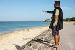 Man on vacation in Japan 6. Man on seawall on vacation in Japan with T shirt looking out over ocean Stock Images