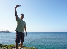 Man on vacation in Japan 9. Man on seawall on vacation in Japan with T shirt taking selfie Royalty Free Stock Photo
