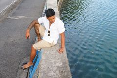 Man on seawall on vacation. In Japan with white shirt 1 Stock Photography