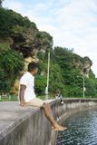 Man on seawall on vacation. In Japan with white shirt 4 Royalty Free Stock Photography