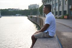 Man on seawall on vacation. In Japan with white shirt 3 Royalty Free Stock Image