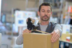 Man securing order inside box. Man securing the order inside the box Royalty Free Stock Images