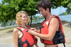 Man securing partner`s lifejacket royalty free stock image