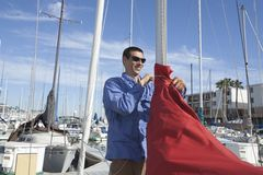 Man Securing Sail Of Boat Royalty Free Stock Images