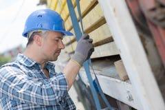 Man securing straps to side lorry. Man securing straps to side of lorry Stock Photo
