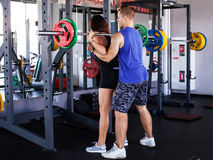 Man securing woman with the barbell Royalty Free Stock Image