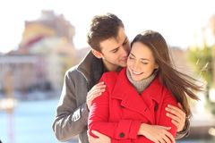 Man seducing a woman whispering on ear. Man seducing a women whispering on ear in a town street in winter holiday royalty free stock image