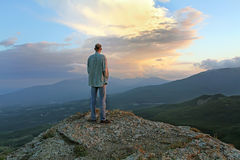 Man sees the approach of change and thunderstorms. human fear of. A man stands on top of the evening and looking at the village beneath the mountain Royalty Free Stock Photos