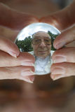 Man sees old age  crystal ball. Man holding a crystal ball at his fingertips and seeing himself at a time in the future as an elderly person Royalty Free Stock Images