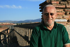 Man in Segovia. A senior man enjoys exploring Segovia, Spain and poses by its famous Roman aqueduct royalty free stock photos