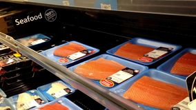 Man selecting atlantic salmon fillet inside Walmart store Royalty Free Stock Image