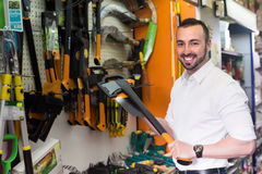 Man selecting axe in household store Stock Photography