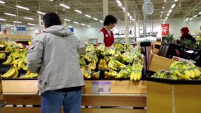 Man selecting banana in grocery store stock video