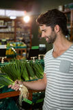 Man selecting a bunch of scallions in organic section Stock Photo