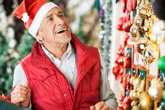 Man Selecting Christmas Ornaments At Store Royalty Free Stock Images