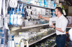 Man selecting electric socket. Young man selecting electric socket in household department Royalty Free Stock Images